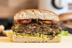 Veggie-Burger auf dem Patty mit Senf, BBQ-Sauce, Salat und Tomaten